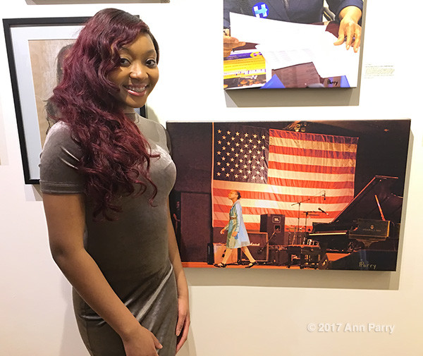 "Huntington, New York, USA. March 5, 2017. Sheimyrah Mighty, 18, next to 2008 photo of herself by Ann Parry, at Opening Reception for ""Her Story Through Art"" Invitational Art Show, celebrating Women's History Month, at Huntington Arts Council, Main Street Gallery."