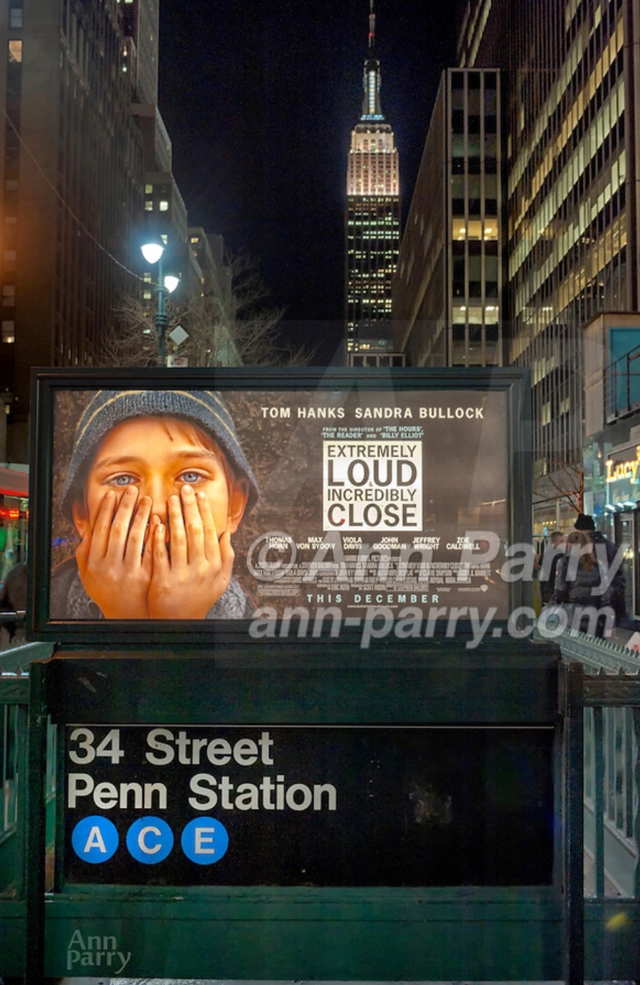 "Manhattan, NY, USA - January 9, 2012: Movie poster ""Extremely Loud & Incredibly Close"" hangs illuminated at night over Penn Station subway entrance with Empire State Building in background. Fictional movie is set at time of 9/11 terrorist attacks on Twin Towers in NYC."