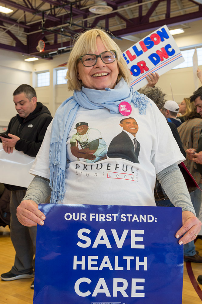"Westbury, New York, USA. January 15, 2017. NANCY BERGER, of Merrick, is holding an ""OUR FIRST STAND: SAVE HEALTH CARE"" poster and wearing a shirt with President Obama's picture on it, at the ""Our First Stand"" Rally against Republicans repealing the Affordable Care Act, ACA, taking millions of people off health insurance, making massive cuts to Medicaid, and defunding Planned Parenthood. It was one of dozens of nationwide Bernie Sanders' rallies for health care that Sunday."