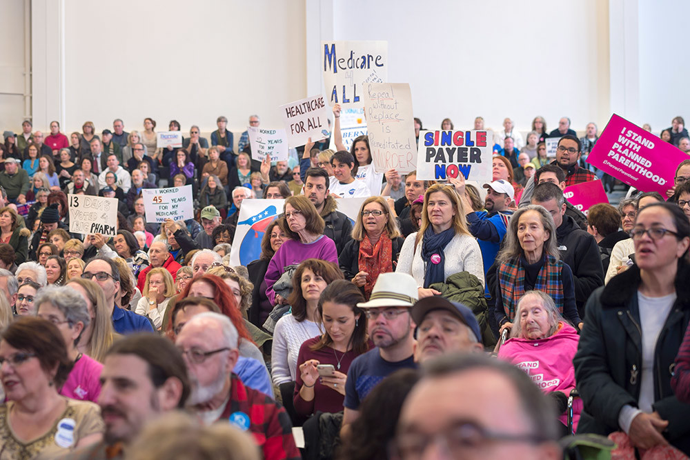 "Westbury, New York, USA. January 15, 2017. Hundreds of people, many with protest signs, are in the audience at the ""Our First Stand"" Rally against Republicans repealing the Affordable Care Act, ACA, taking millions of people off health insurance, making massive cuts to Medicaid, and defunding Planned Parenthood. It was one of dozens of nationwide Bernie Sanders' rallies for health care that Sunday."