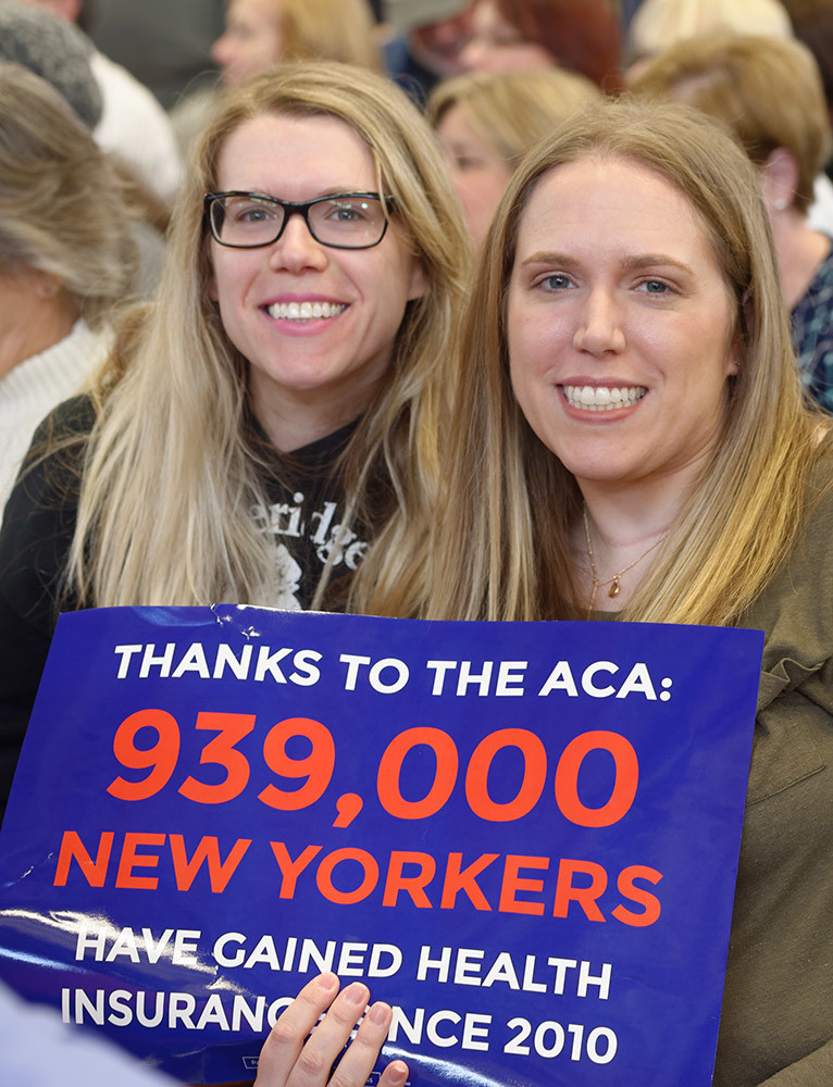 "Westbury, New York, USA. January 15, 2017. L-R, sisters LAUREN GRAB and SUE MOLLER, both from Long Island, hold sign ""Thanks to the ACA 939,000 NEW YORKERS have gained health Insurance since 2010"" at the ""Our First Stand"" Rally against Republicans repealing the Affordable Care Act, ACA, taking millions of people off health insurance, making massive cuts to Medicaid, and defunding Planned Parenthood. Hosts were Reps. K. Rice (Democrat - 4th Congressional District) and T. Suozzi (Dem. - 3rd Congress. Dist.)."