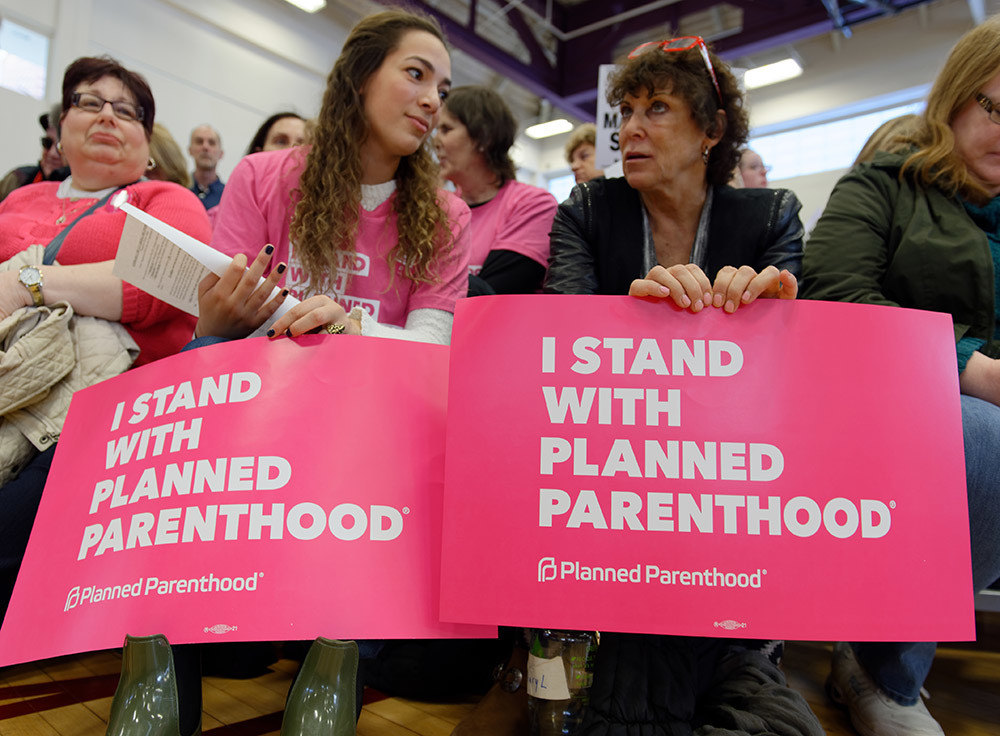 "Westbury, New York, USA. January 15, 2017. L-R, Rabbi JUDITH COHEN-ROSENBERG, of Westbury; and KASSANDRA POLANCO of Massapequa, and CHERYL SCHRUEFER, of Hicksville, wear pink shirts and/or buttons and hold pink ""I STAND WITH PLANNED PARENHOOD"" signs at the ""Our First Stand"" Rally against Republicans repealing the Affordable Care Act, ACA, taking millions of people off health insurance, making massive cuts to Medicaid, and defunding Planned Parenthood. Hosts were Reps. K. Rice (Democrat - 4th Congressional District) and T. Suozzi (Dem. - 3rd Congress. Dist.)."