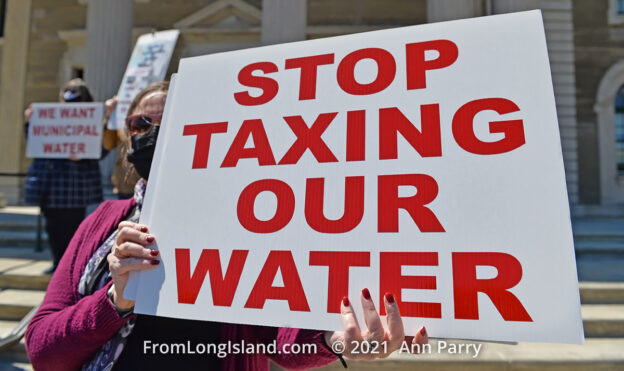 Mineola, New York, USA. April 26, 2021. Activist at rally holds sign saying: STOP TAXING OUR WATER. Faced with a 26% rate increase from New York American Water going into effect May 1, 2021, activists and residents who are NYAW customers rally to urge NYS Assemby to push through legislation, before that date, corresponding with NYS Senate Bill S989A to establish a Nassau County Water Authority and except water works corporations in counties of populations over one million from a special franchise tax. (© 2021 Ann Parry, AnnParry.com)