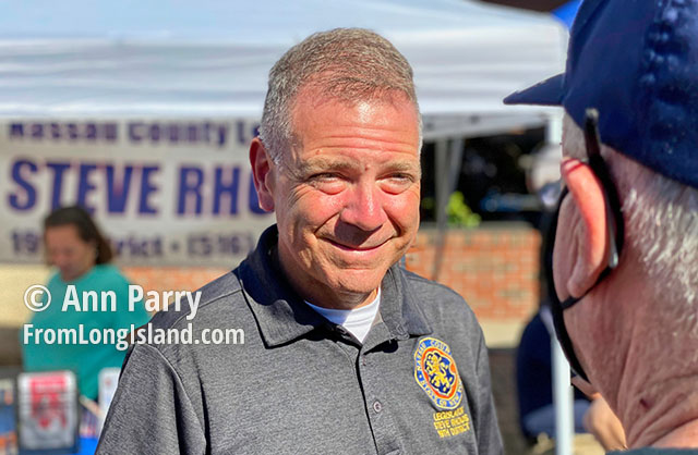 Bellmore, NY, U.S. Sept. 25, 2021. New York State Legislator STEVE RHOADS (R-19th District) speaks with a visitor at the 34th Annual Bellmore Family Street Festival.